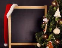 Tableau noir avec le chapeau d'arbre et de Santa de Noël Photographie stock libre de droits