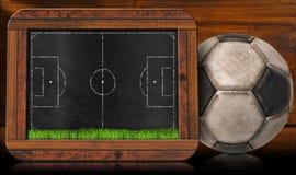 Tableau noir avec le terrain de football et la boule Images stock