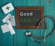 Tableau noir avec le texte et le x22 ; Bon Health& x22 ; , pilules et stéthoscope Photographie stock libre de droits