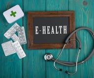 Tableau noir avec le texte et le x22 ; E-health& x22 ; et stéthoscope sur le fond en bois bleu Image stock