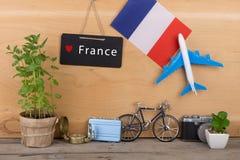tableau noir avec le texte et le x22 ; France& x22 ; , drapeau des Frances, modèle d'avion, peu de bicyclette et valise, appareil Photo libre de droits
