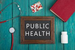 Tableau noir avec le texte et le x22 ; Health& public x22 ; , pilules, livre et stéthoscope sur le fond en bois Photographie stock