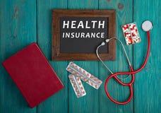 Tableau noir avec le texte et le x22 ; Insurance& x22 de santé ; , livre, pilules et stéthoscope sur le fond en bois bleu Image libre de droits