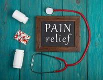 Tableau noir avec le texte et le x22 ; Relief& x22 de douleur ; , pilules et stéthoscope sur le fond en bois images stock