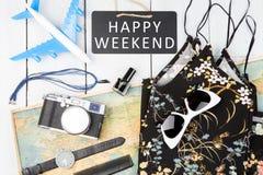 tableau noir avec le texte et le x22 ; WEEKEND& HEUREUX x22 ; , avion, carte, lunettes de soleil, montre, appareil-photo Photos libres de droits