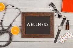 Tableau noir avec le texte et le x22 ; Wellness& x22 ; , pilules, livre et stéthoscope Images libres de droits