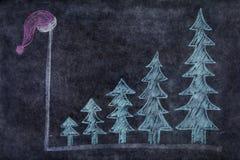 Tableau noir avec les arbres de Noël et le chapeau de Santa Photographie stock libre de droits