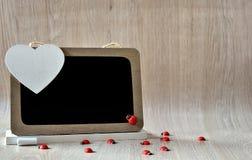 Tableau noir avec les coccinelles rouges et le coeur blanc Images libres de droits