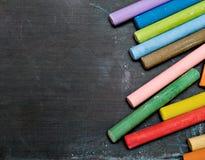 Tableau noir avec les crayons colorés Photo stock