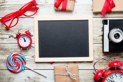 Tableau noir, cadeaux, appareil-photo, lucette et verres Image stock