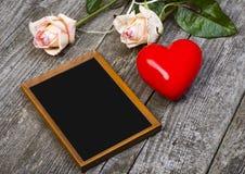 Tableau noir, coeur rouge et roses Images stock