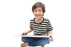 Tableau noir d'écriture de petit garçon avec le sourire sur le blackground de whoite Photos stock