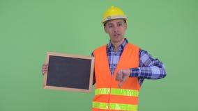Tableau noir de participation de travailleur de la construction d'homme et de donner pouces ethniques multi soumis à une contrain banque de vidéos