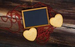 Tableau noir et deux biscuits en forme de coeur Image stock