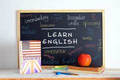 Tableau noir et matériel d'école dans un cours d'anglais Photo stock