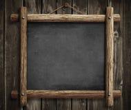 Tableau noir grunge accrochant sur le fond en bois de mur Photographie stock libre de droits