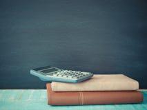Tableau noir, livres et calculatrices avec l'espace libre pour le texte Photos libres de droits