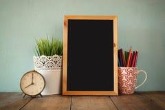 Tableau noir, pile de crayons colorés et horloge De nouveau au concept d'école Image libre de droits