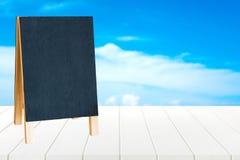 Tableau noir sur le fond de table en bois et de ciel bleu Photographie stock