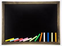 Tableau noir vide avec les craies colorées de domino Images libres de droits