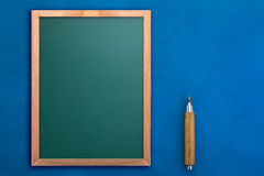 Tableau vide avec le crayon sur le fond bleu jpg Images stock