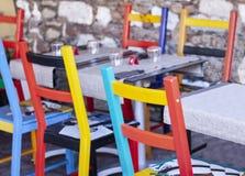 Tableaux avec les chaises multicolores sur la terrasse dans un café dans Taormina, Sicile, Italie photos libres de droits