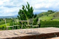 Tableaux et chaises sur la vue gentille de terrasse au-dessus de la montagne Images stock