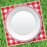 Tablecloth and empty plate on green grass, vector  Stock Image