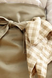 Tablecloth hanging from the waist of a tied apron Stock Images