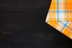 Tablecloth. The plaid tartan tablecloth on black wooden table in top view Royalty Free Stock Photo