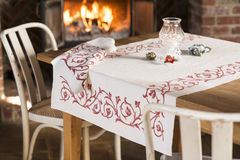 Tablecloth with Red Floral Design on Table near Blazing Fireplac. A white tablecloth or linen with red floral pattern design laid spread out on a wooden dining Stock Photo