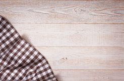 Tablecloth tartan on white wooden table. Flat mock Stock Photos