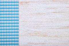 Tablecloth textile texture on wooden background. Blue checkered tablecloth textile on white wooden table background Stock Image