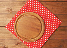 Tablecloth or towel over the wooden table. Red polka dot tablecloth or towel over the surface of a brown wooden table with a round wooden tray on top of it Royalty Free Stock Photos