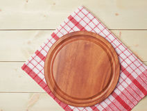 Tablecloth or towel over the wooden table. Red tablecloth or towel over the surface of a wooden table with a round wooden tray on top of it Stock Image