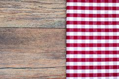 Tablecloth in white and red cage on wooden table. Studio Photo Stock Images