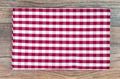 Tablecloth in white and red cage on wooden table. Studio Photo Stock Photos