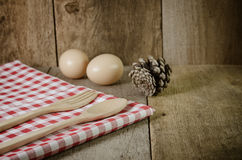 Tablecloth, wooden spoon, fork on wood textured background Royalty Free Stock Photos