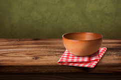 Tablecloths and soup bowl over wooden table. Folded tablecloth on wooden table and wooden soup bowl Stock Images