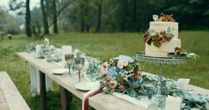 Tabler在有薄雾的森林花鲜美两层蛋糕和花束的浪漫日期服务在装饰的桌上 股票录像