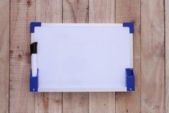 Tablero blanco con el fabricante coloreado en el fondo de madera Foto de archivo libre de regalías