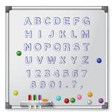 Tablero blanco con los marcadores coloreados y alfabeto Foto de archivo