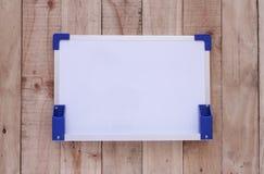 Tablero blanco en el fondo de madera Imagen de archivo libre de regalías