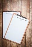 Tablero con el documento en blanco sobre fondo de madera Imagen de archivo