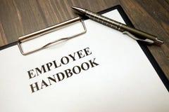 Tablero con el manual del empleado y pluma en el escritorio fotografía de archivo