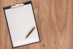 Tablero con el papel en blanco y pluma en el escritorio de madera Imagenes de archivo