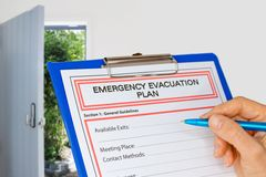 Tablero con el plan de evacuación de la emergencia al lado de la puerta de salida Imagenes de archivo