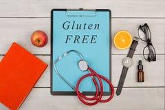 tablero con el texto y x22; Free& x22 del gluten; , libro, lentes, reloj, fruta y estetoscopio Imagen de archivo libre de regalías