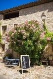 Tablero con la escritura del bonjour delante del café francés Foto de archivo