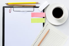 Tablero con la hoja del banco y la taza de café en la tabla blanca Imagen de archivo libre de regalías